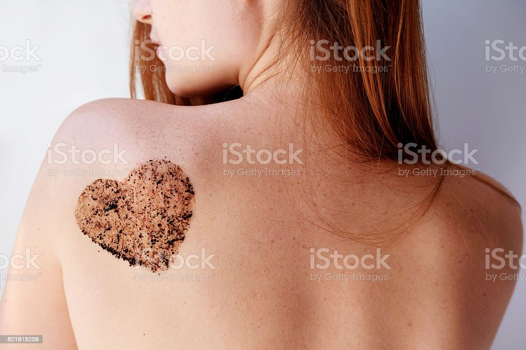 Woman with coffee scrub in a heart shape on back. stock photo