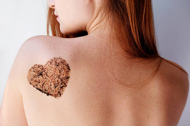 woman with coffee scrub in a heart shape on back. - exfoliant photos et images de collection