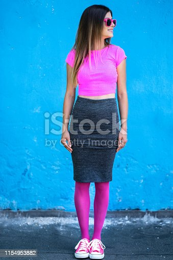 istock Woman with color outfit standing on blue background 1154953882