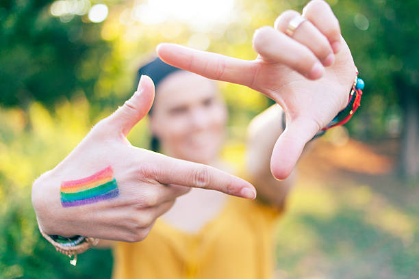 woman with colored flag on hand making finger frame - transsexual stock photos and pictures