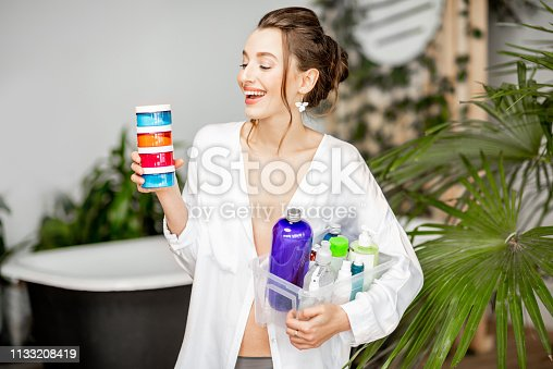 Portrait of a young and happy woman holding lots of colorful bottles with different liquids for self-care in the bathroom