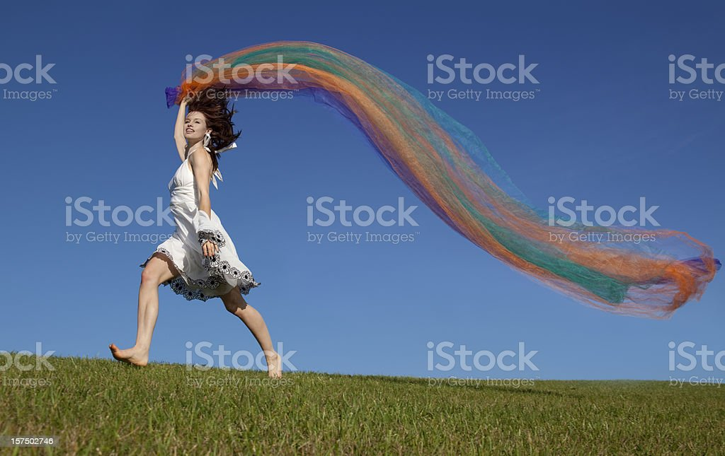Woman With Colorful Fabric Running on Hilltop royalty-free stock photo