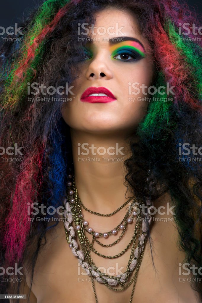 Sexy fashion model with unusual curly colorful hair. About 20 years...