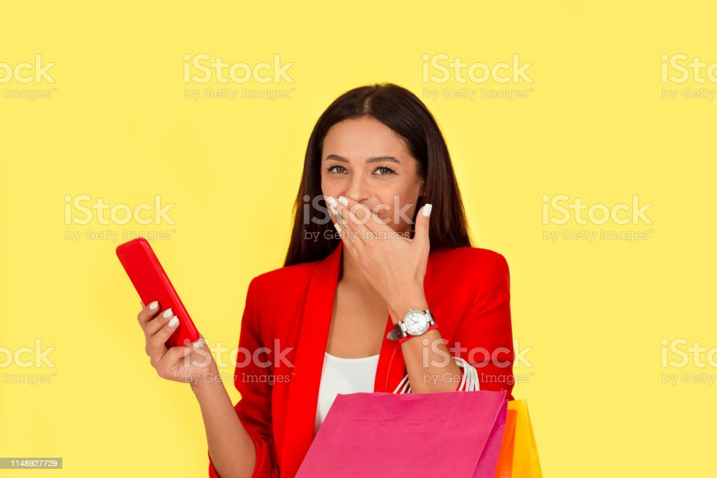 Portrait of a pretty excited woman with colorful shopping bags...