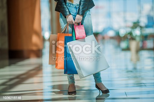 Sale and people - smiling woman with colorful shopping bags over supermarket background