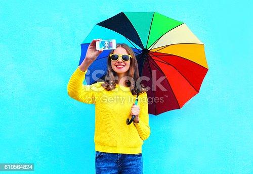 istock woman with colorful umbrella taking autumn self portrait on smartphone 610564824