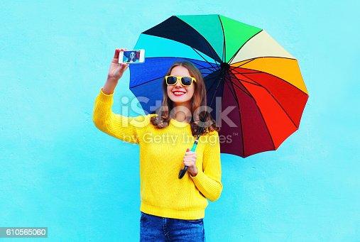 istock woman with colorful umbrella taking autumn self portrait on smartphone 610565060