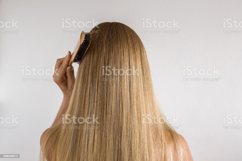 Woman with comb brushing her dry blonde hair on the gray background. Cares about a healthy and clean hair. Beauty salon concept. stock photo