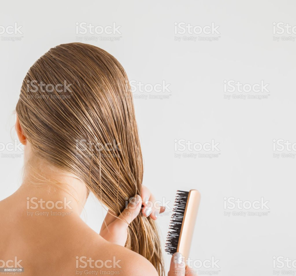 Woman with comb brushing her wet blonde hair after shower on the gray background. Cares about a healthy and clean hair. Beauty salon concept. stock photo