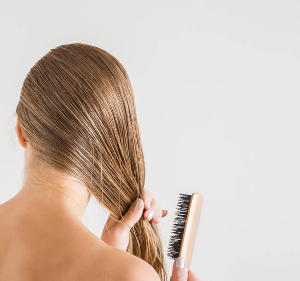 woman with comb brushing her wet blonde hair after shower on the gray background. cares about a healthy and clean hair. beauty salon concept. - capelli ossigenati foto e immagini stock