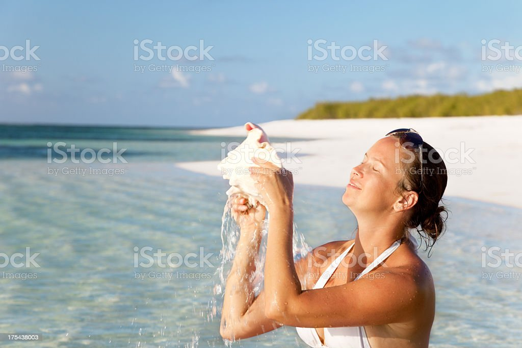 woman with conch shell at a tropical Caribbean beach stock photo