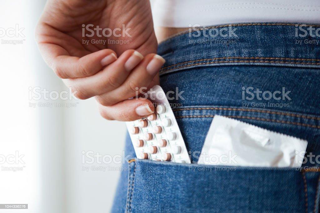 Mulher com pílulas anticoncepcionais e camisinha no bolso das calças de brim azul. - foto de acervo