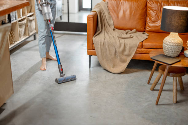Woman with cordless vacuum cleaning floor at home stock photo