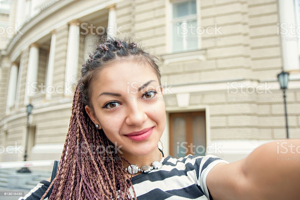Woman with cornrows dreads making selfie at the street stock photo