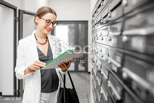 istock woman with correspondence near the mailboxes 1065781900
