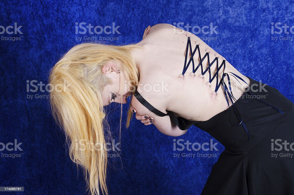 Woman with corset piercing bending at waist. stock photo