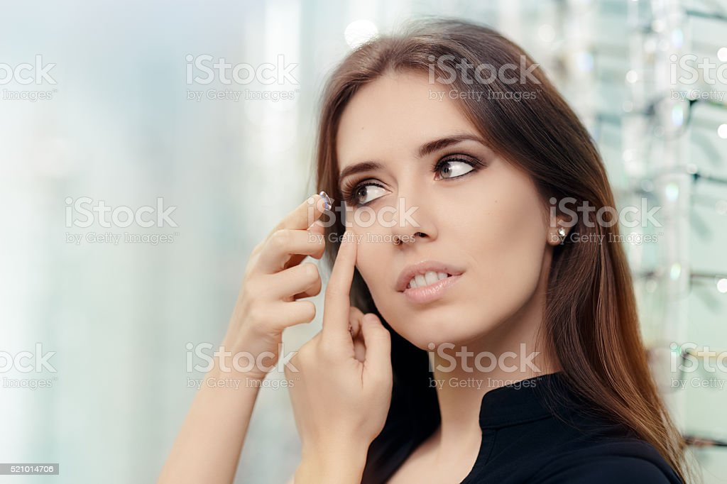 Woman with Cosmetic Colored Lenses in Optical Store stock photo