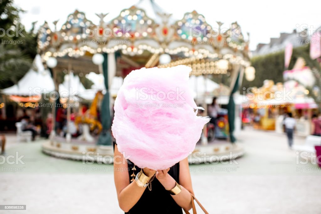 Woman with cotton candy at the amusement park stock photo
