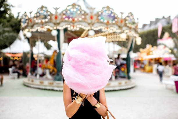 Woman with cotton candy at the amusement park Young woman standing with pink cotton candy outdoors in front of the carrousel at the amusement park amusement park stock pictures, royalty-free photos & images