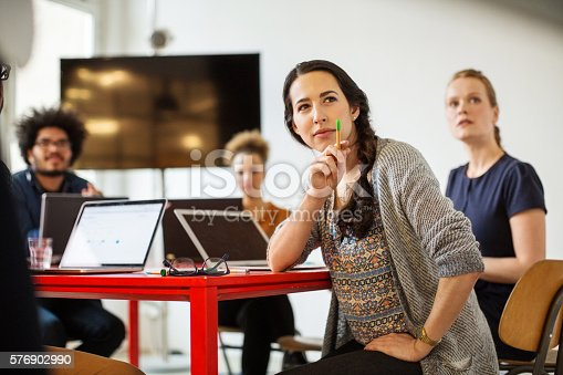 Woman looking at the presentation with coworkers sitting at back in conference room
