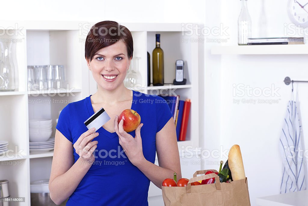 Woman with credit card and shopping bag in the kitchen royalty-free stock photo