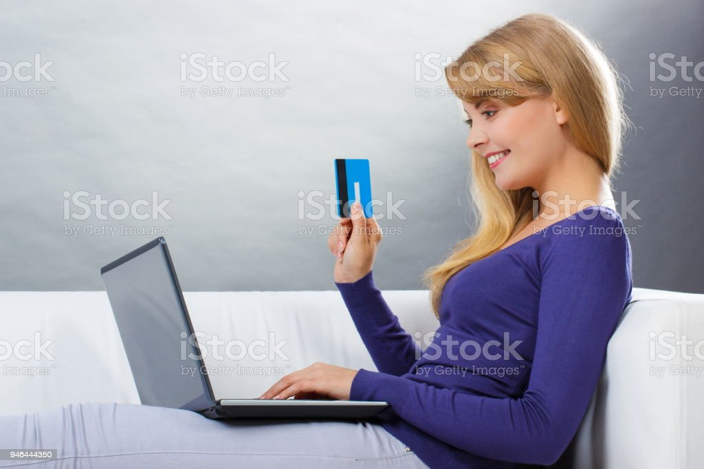 Woman with credit card paying over internet for online shopping stock photo