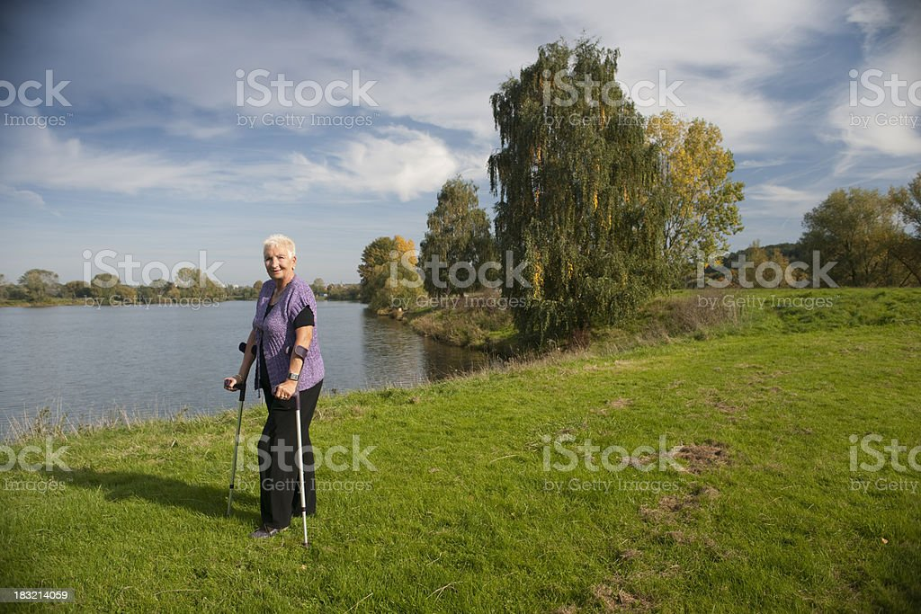 Woman with crutches in autumn landscape stock photo