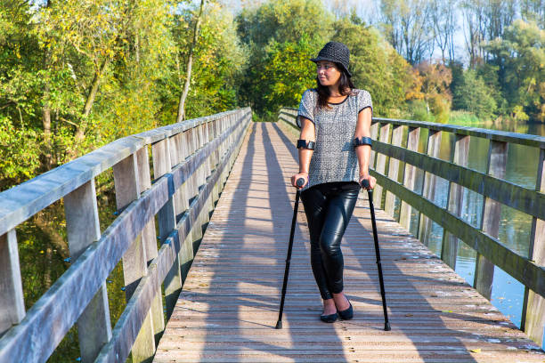 Woman with crutches standing on bridge stock photo