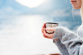 Woman with cup of coffee by winter sea, blue mountains. Cozy picnic with thermos of hot steamy beverage tea on beach. Girl is enjoying nature, life, relaxation, Christmas mood.