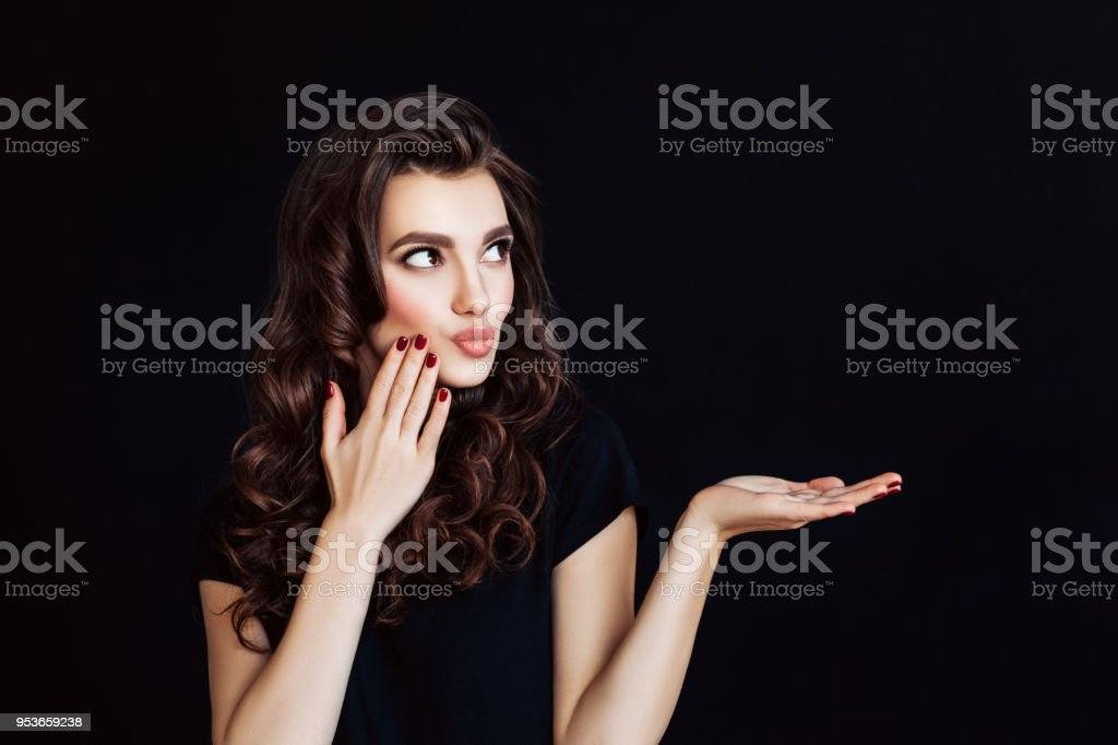 Woman with curly brown hair represents an imaginary product stock photo