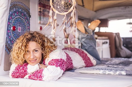 woman with curly hair and red and white striped warm sweater looks and smiles relaxed inside her van. Concept of freedom, vacation and independence