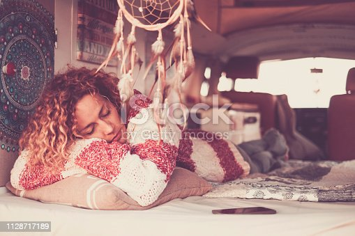 woman with curly hair and warm sweater sleeping and dreaming on home van, lulled by the sea breeze. Concept of independence, relaxation, travel, leisure time - dreamcatcher and vintage filter