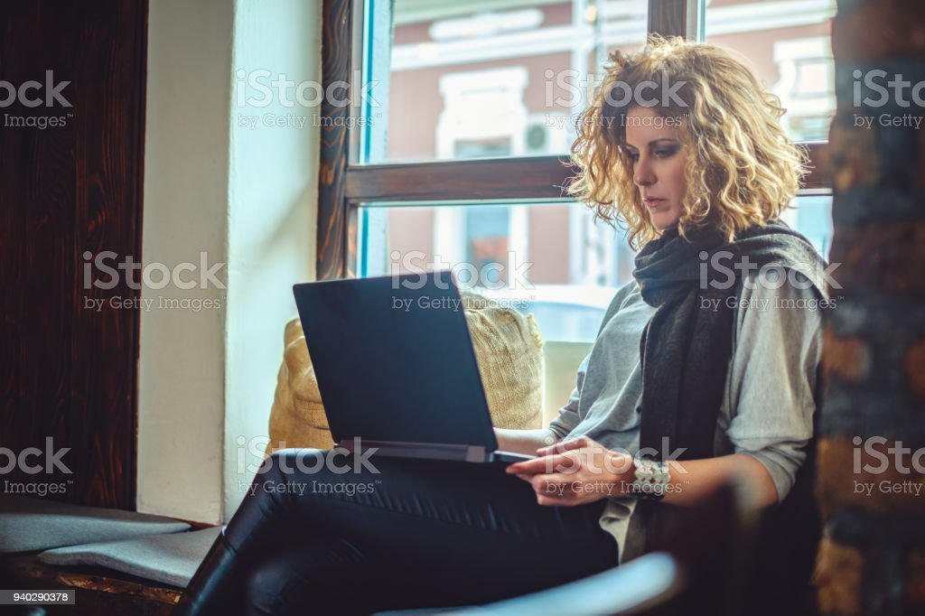 Woman with curly hair working seriously on her laptop Woman with curly hair working seriously on her laptop in a cafe Adult Stock Photo