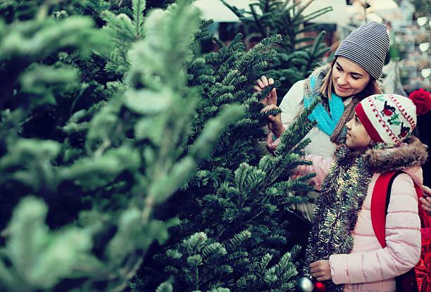 woman with daughter buying christmas tree in market - günstige weihnachtsgeschenke stock-fotos und bilder
