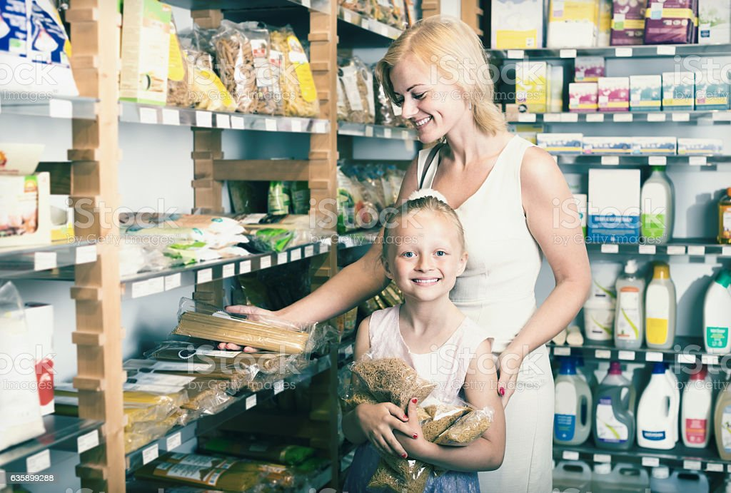 woman with daughter buying pasta in store stock photo