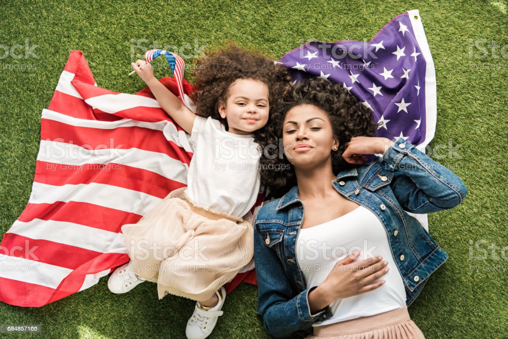 woman with daughter on american flag stock photo