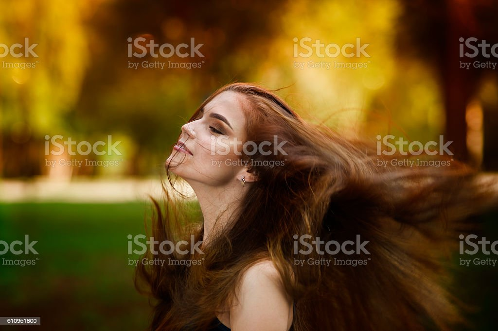 Woman with developing in the wind long hair, autumn season stock photo