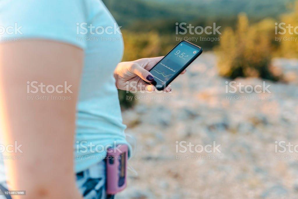 Frau mit Diabetes tragen einer Insulinpumpe und überprüfen ihr Blutzucker auf eine Smartphone-app – Foto