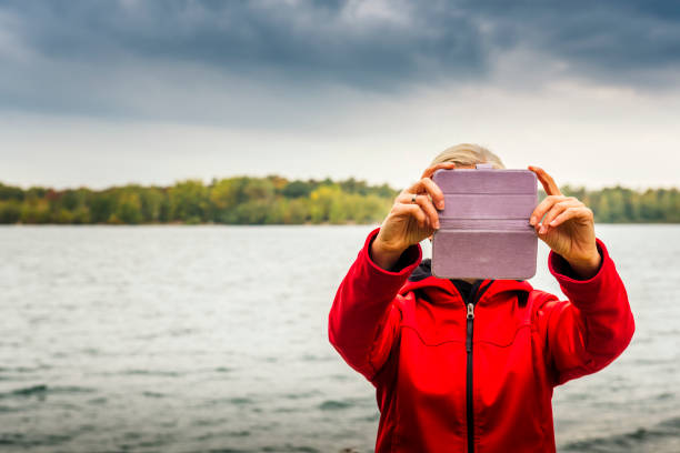 Frau mit Digitalkamera unter Selfies auf einem See – Foto