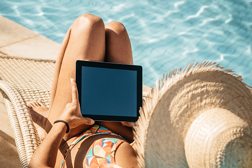 woman with digital tablet at swimming pool
