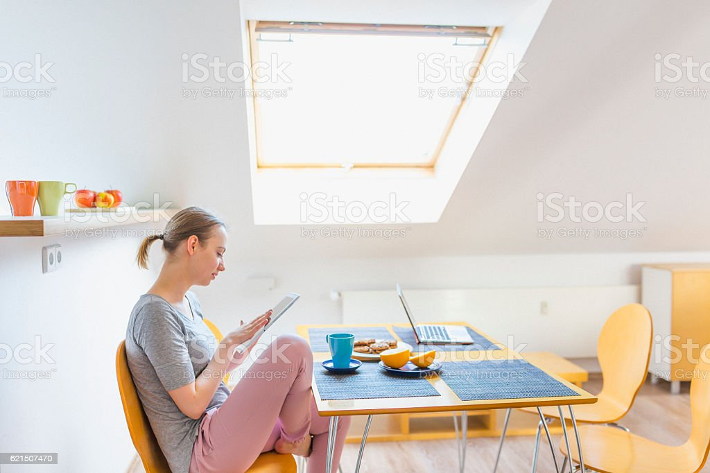 Woman with digital tablet during breakfast at home photo libre de droits