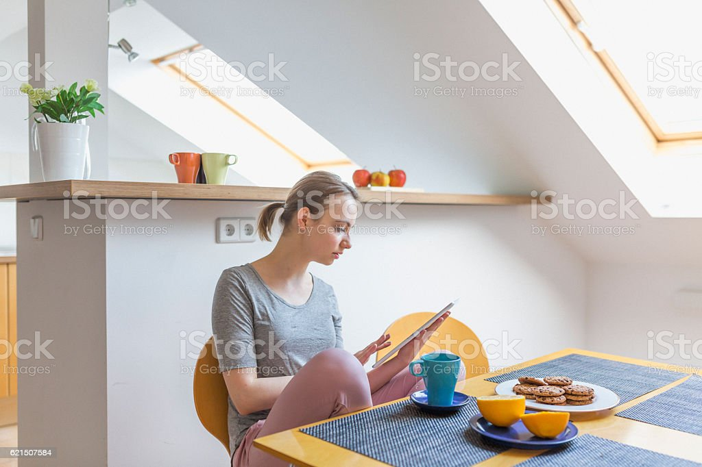 Woman with digital tablet during breakfast at home Lizenzfreies stock-foto