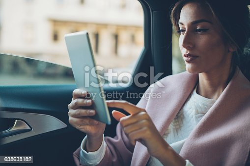 istock Woman with digital tablet in a car 638638182
