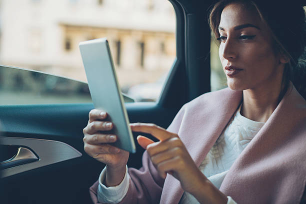 Woman with digital tablet in a car stock photo