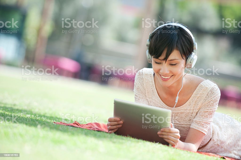 Woman with digital tablet in the park stock photo