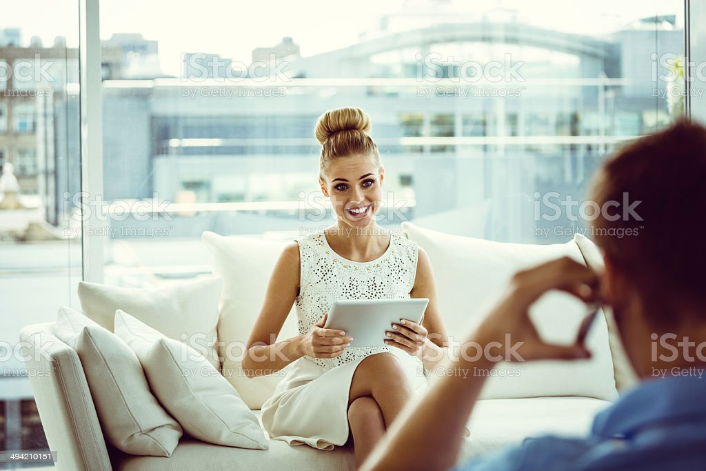 Woman with digital tablet Focus on young woman sitting on sofa at home and using a digital tablet with the back side view of a men talking on phone on the foreground. Couple - Relationship Stock Photo