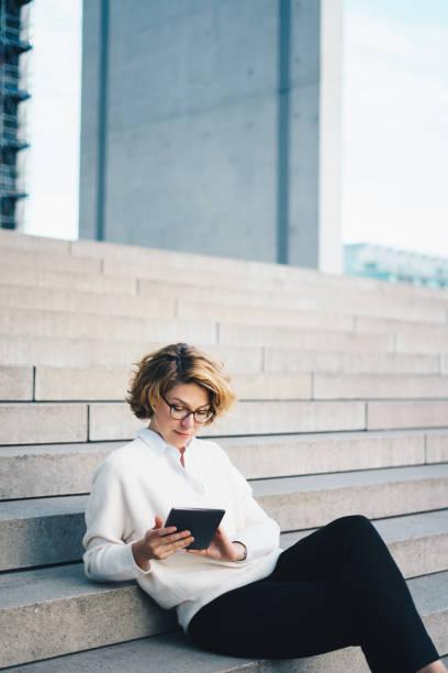 frau mit digital-tablette sitzen auf den stufen im freien - brille bestellen stock-fotos und bilder