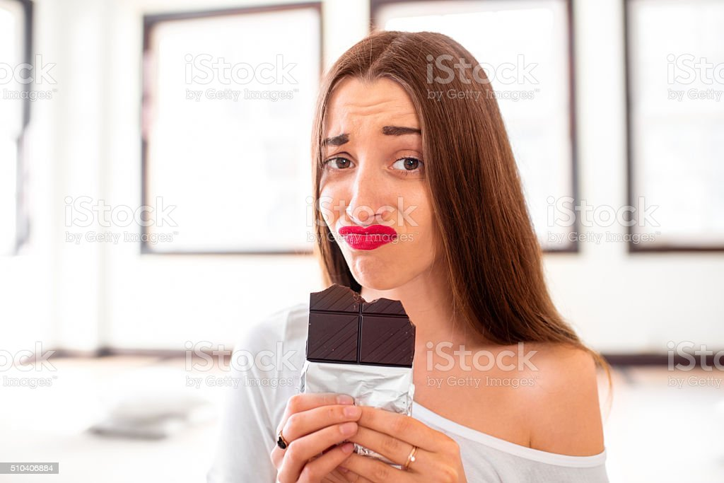 Woman with disappointed emotions holding chocolate - Royalty-free Adult Stock Photo