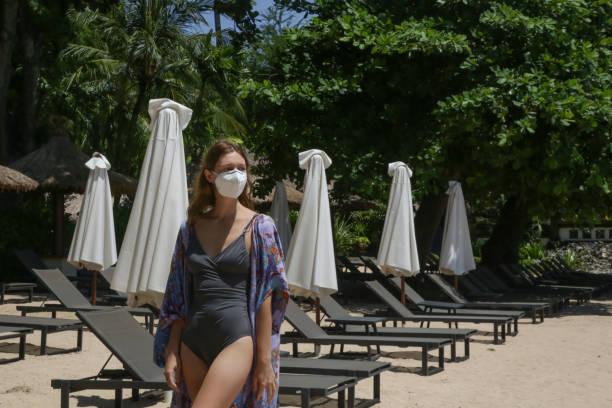 Frau mit Einweg-OP-Maske allein am Strand. Leerer Strand während der Coronavirus-Sperre. Coronavirus-Pandemiekrise. Der Tourismus befindet sich aufgrund der weltweiten Panik vor dem Corona-Virus in einer großen Krise. – Foto