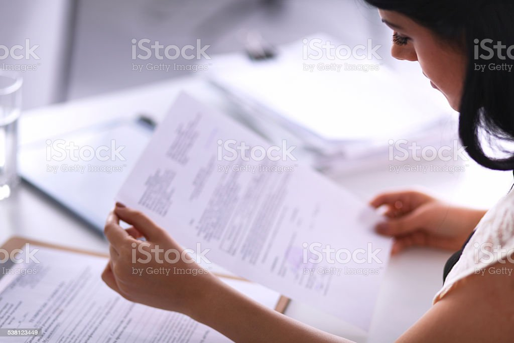 Woman with documents sitting on the desk stock photo